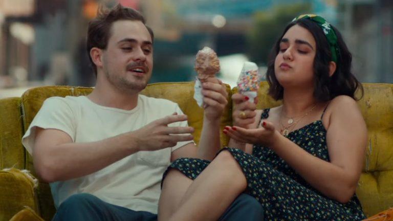 Casal sentado comendo sorvete em um sofá velho no meio da rua