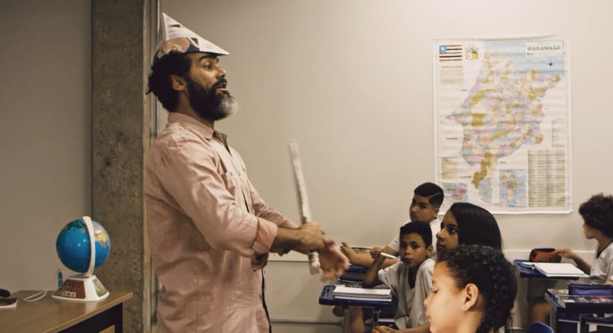Temos um professor, dando um aula de maneira dinâmica, incorporando personagem de um revolucionários,usando um chapéu e uma espada de papel em Escola Sem Sentido.