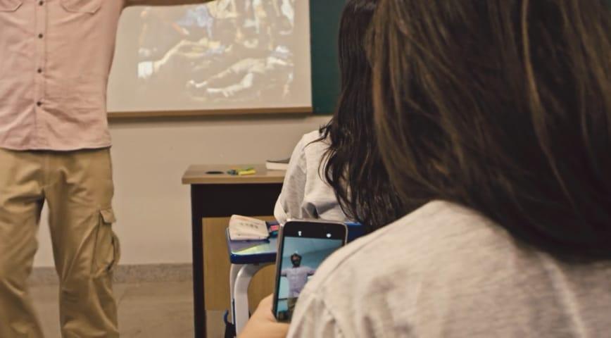 Aluna com celular, enquanto professor dá aula