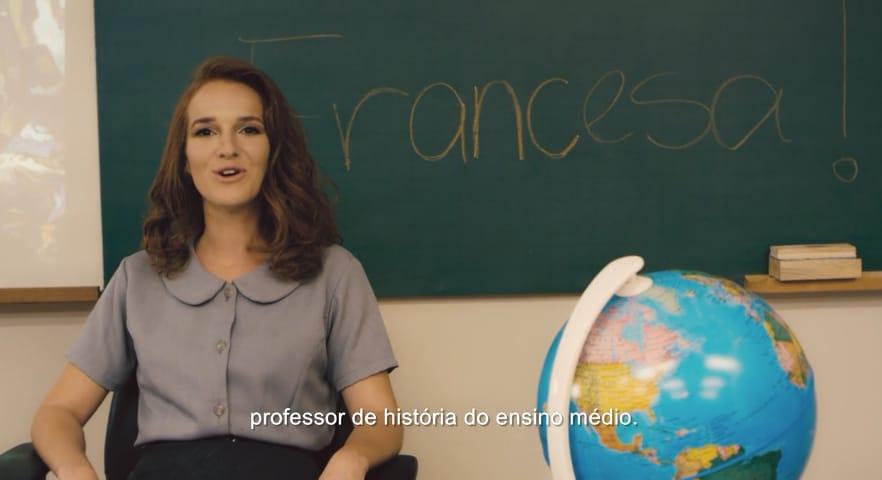 Personagem falando com a câmera, em uma sala de aula. Legenda na parte de inferior da imagem. Escola Sem Sentido