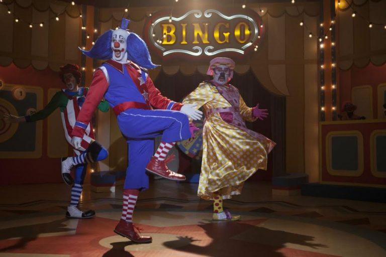 Palhaço dançando com duas pessoas vestidas de animais
