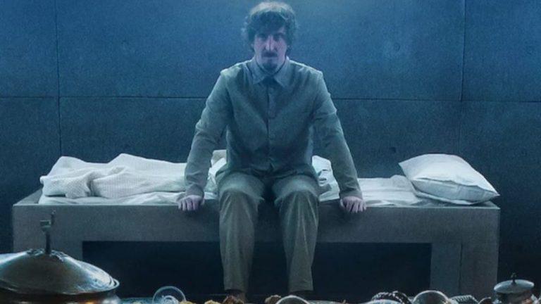 Homem sentado em uma cama dentro da cela.