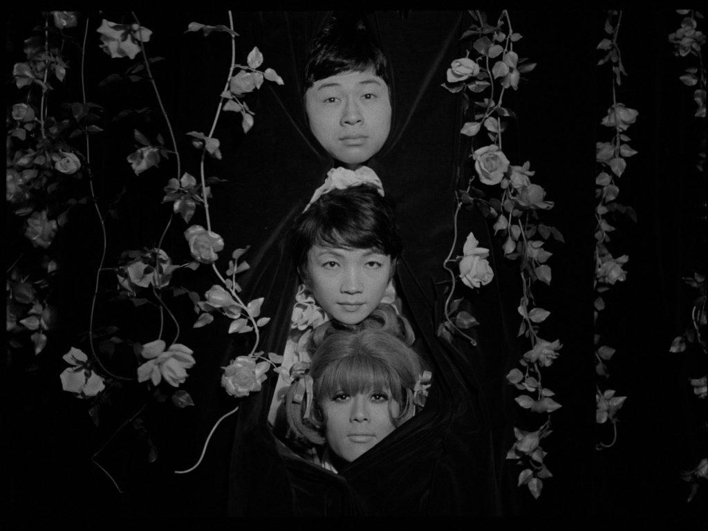 Três protagonistas do filme estão no centro da imagem, se encontram em um cenário de teatro, com suas cabeças envoltas por uma cortina de cor escura. Funeral das Rosas Otageek