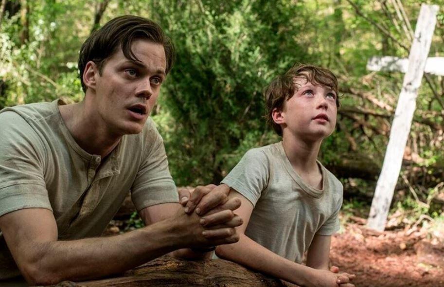 Willard Russell (Bill Skarsgård) rezando com seu filho