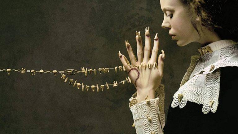 Mulher com roupa de colonizadora e com dentes cravados nas mãos e nas unhas