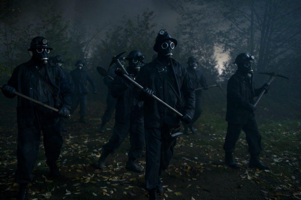 Mineiros  com roupas e mascara pretas, segurando sua picaretas, andando pela floresta