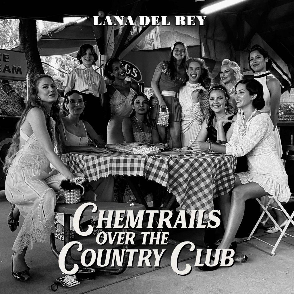 A cantora Lana Del Rey em pé em frente a uma mesa com suas amigas sentadas na capa do album Chemtrails Over The Country Club. Otageek