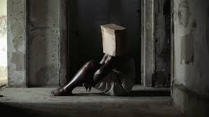 Mulher preta sentada no chão, com as mãos em torno das pernas e a cabeça encoberta por um pacote.