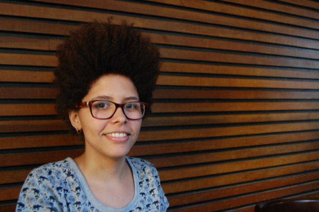 Mulher preta com óculos e sorrindo